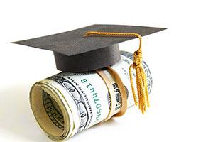 photo of graduation cap on a pile of money