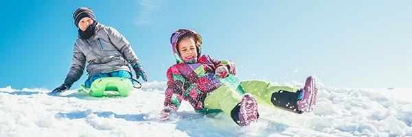 photo of kids sledding down a hill