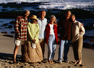 group of adults standing and smiling on beach